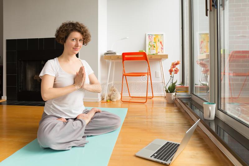 mulher-que-faz-ioga-com-app-em-linha-no-computador-em-sua-sala-de-visitas